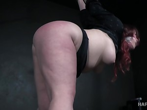 Voluptuous redheaded bitch close to a big ass gets punished by her bondage master